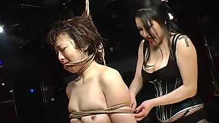 Latex-clad domina whips a bound slavegirl